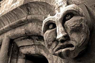 """04.09.12 - Old Stone Face  One of the many joys of photography is finding something """"new"""" right under your nose, or in this case just above my head! I must have walked past this guy thousands of times over the years, but never noticed him. He is one of the better preserved carvings on the Stonebow, the old medieval south gate to the city, which is now smack bang in the centre of town. I've done a contrasty B&W conversion with a sepia filter to bring out the textures in the limestone."""